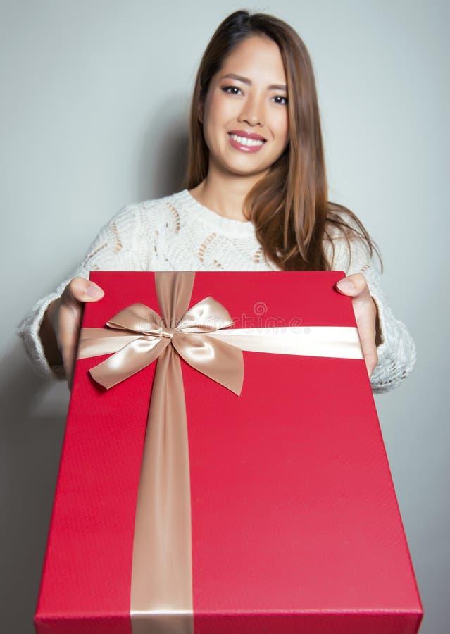 Belle jeune femme asiatique tenant un présent photo stock