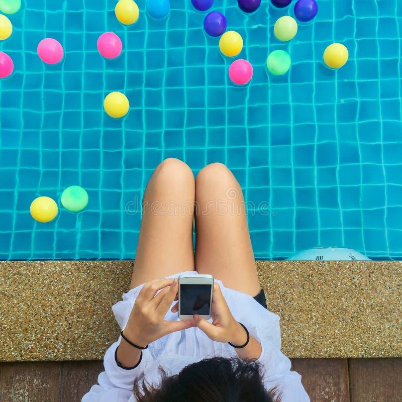 Belle jeune femme avec actualités de lecture de beau sourire de bonnes au téléphone portable se reposant par le poolside images stock