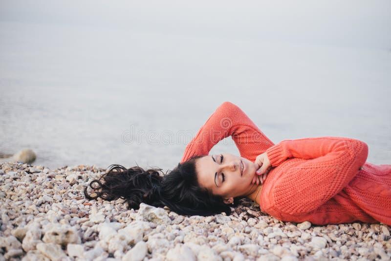 Belle jeune femme avec de longs cheveux bouclés se trouvant sur la plage photographie stock