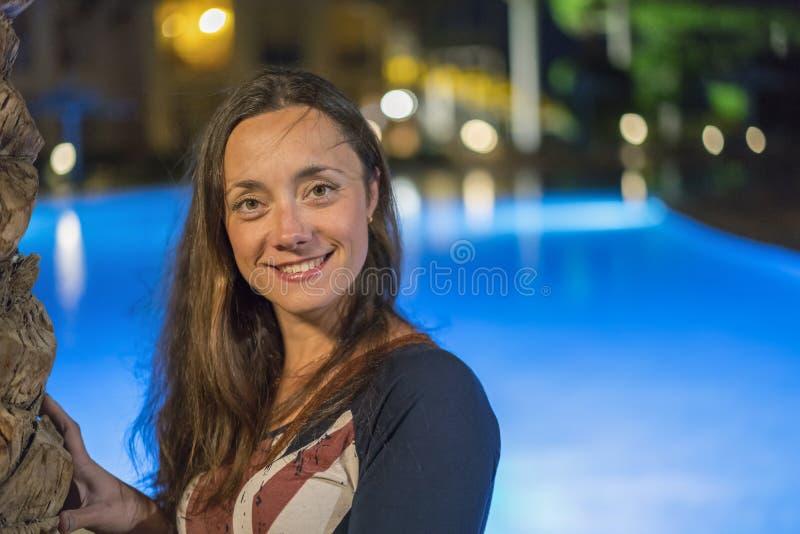 Belle jeune femme avec de longs cheveux près de la piscine de nuit images stock