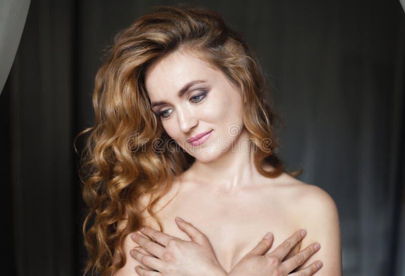 Belle jeune femme avec de longs cheveux sinueux rouges photos stock