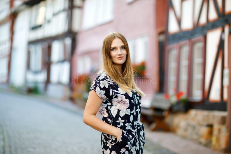 Belle jeune femme avec de longs poils dans la robe d'été faisant une promenade dans la ville allemande Fille heureuse appréciant  photos stock