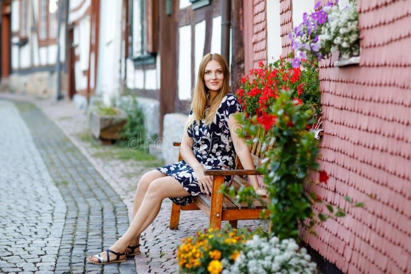 Belle jeune femme avec de longs poils dans la robe d'été faisant une promenade dans la ville allemande Fille heureuse appréciant  photographie stock libre de droits