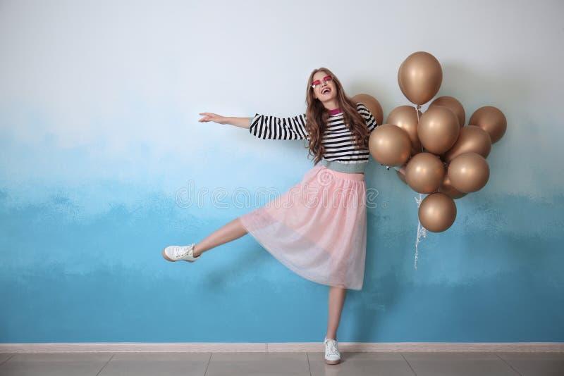 Belle jeune femme avec des ballons près de mur de couleur image stock