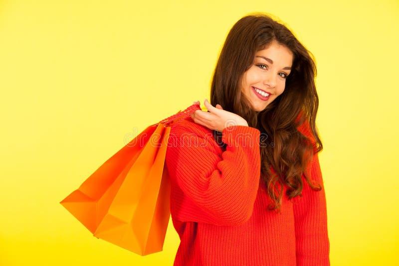 Belle jeune femme avec des paniers au-dessus de CCB vibrant de jaune image stock