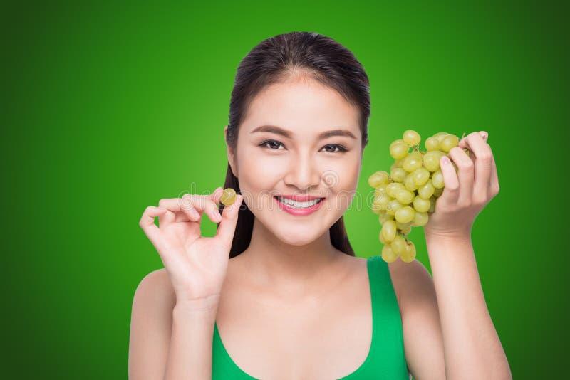 Belle jeune femme avec du raisin vert d'isolement sur le backgro vert photos libres de droits