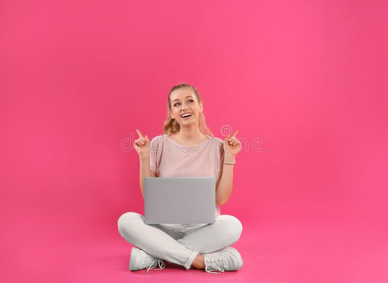 Belle jeune femme avec l'ordinateur portable sur le rose image stock