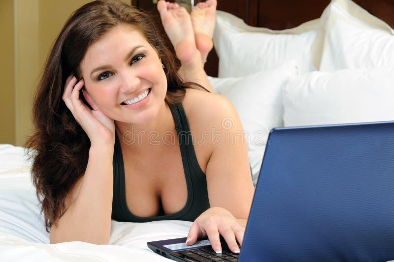 Belle jeune femme avec l'ordinateur portatif dans le bâti image stock