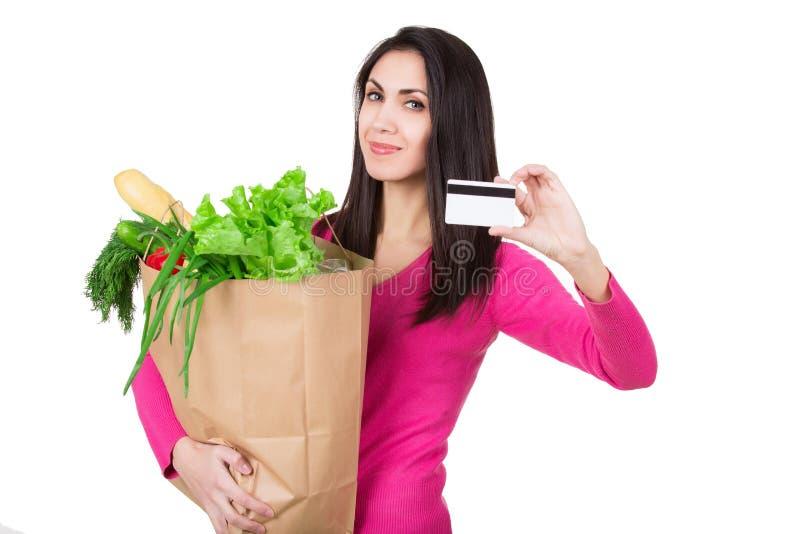 Belle jeune femme avec la carte de crédit tenant le sac de papier avec des épiceries D'isolement Achats et concept d'épiceries image stock