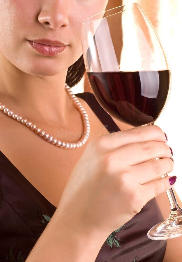 Belle jeune femme avec la glace de vin rouge image libre de droits
