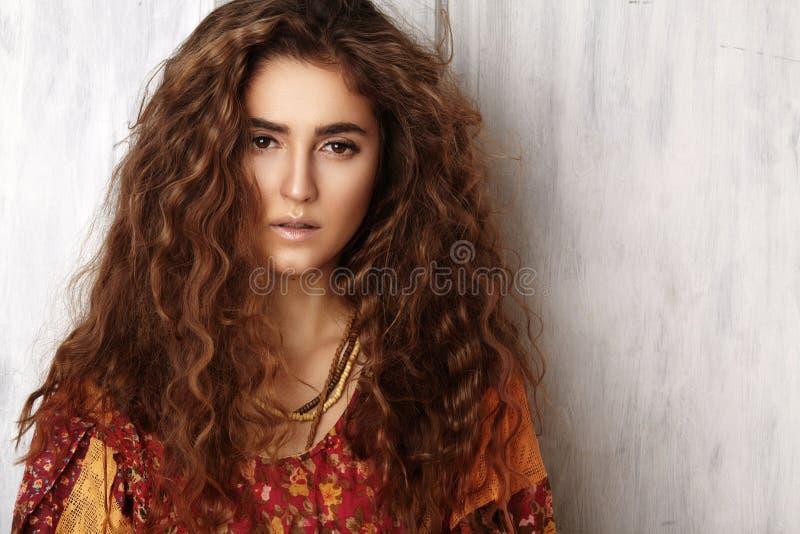 Belle jeune femme avec la longue coiffure bouclée, bijoux de mode avec des cheveux de brune Vêtements indiens de style, longue ro photographie stock libre de droits