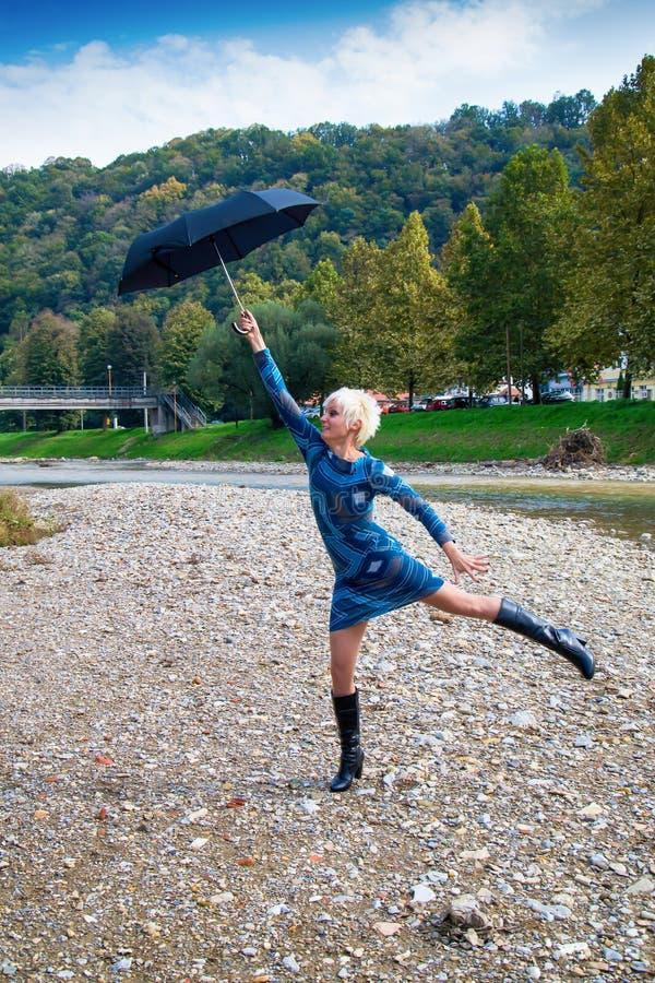 Belle jeune femme avec la mouche de parapluie à l'avenir photos stock