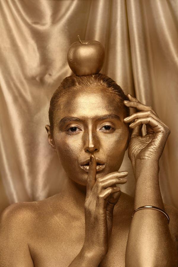 Belle jeune femme avec la peinture d'or sur son corps et pomme sur le fond de couleur photographie stock libre de droits