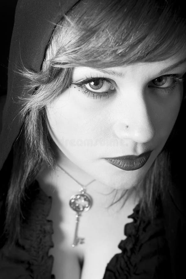 Belle jeune femme avec la robe et le pendant à capuchon de clé Grands yeux intenses photographie stock