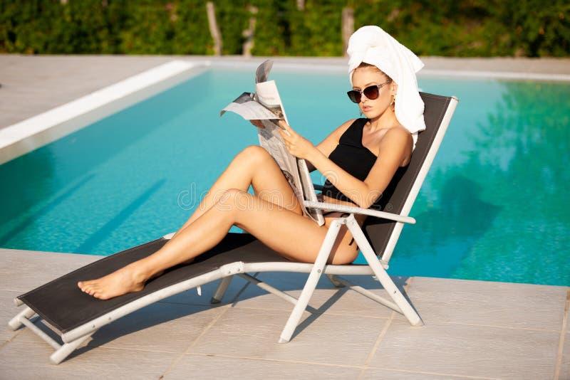 Belle jeune femme avec la serviette sur son journal de lecture de cheveux près de piscine d'hôtel photographie stock
