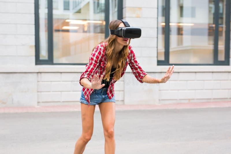Belle jeune femme avec le casque de port de réalité virtuelle de longs cheveux dans un contexte urbain images stock