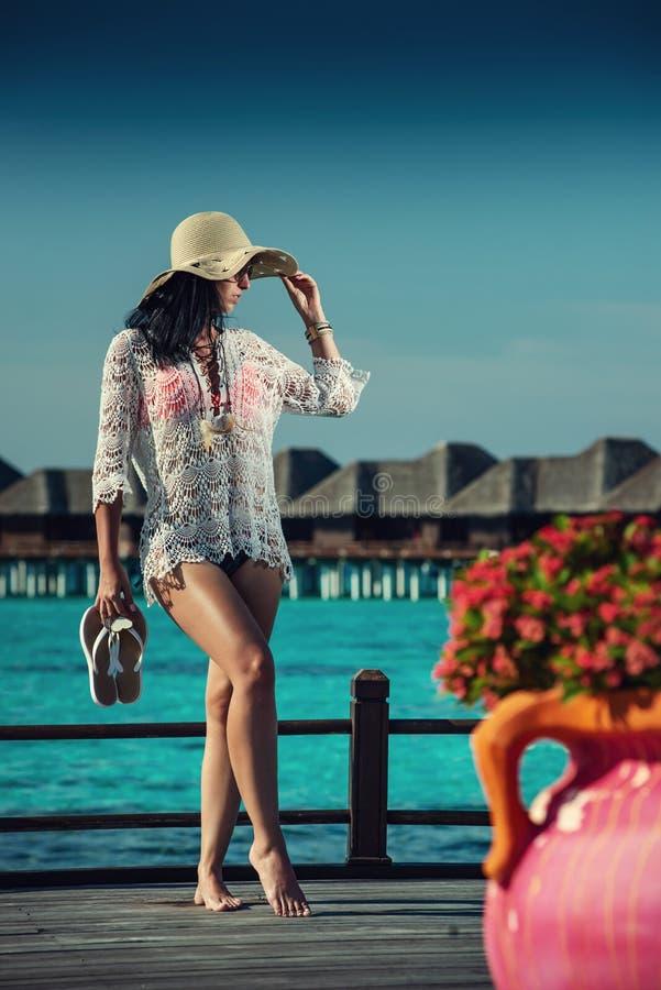 Belle jeune femme avec le chapeau sur la plage blanche, beau paysage avec la femme en Maldives, paradis tropical photos libres de droits