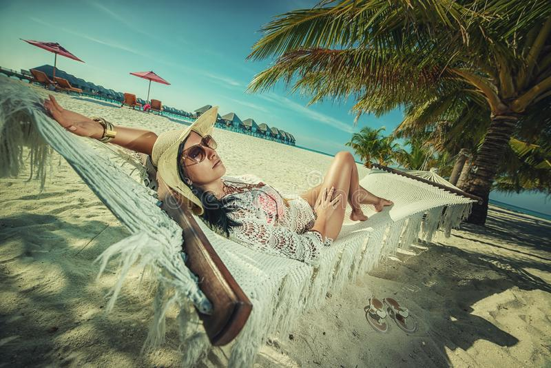 Belle jeune femme avec le chapeau sur la plage blanche, beau paysage avec la femme en Maldives, paradis tropical image libre de droits