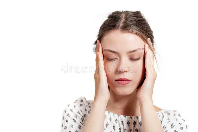 Belle jeune femme avec le mal de tête touchant ses temples photo libre de droits