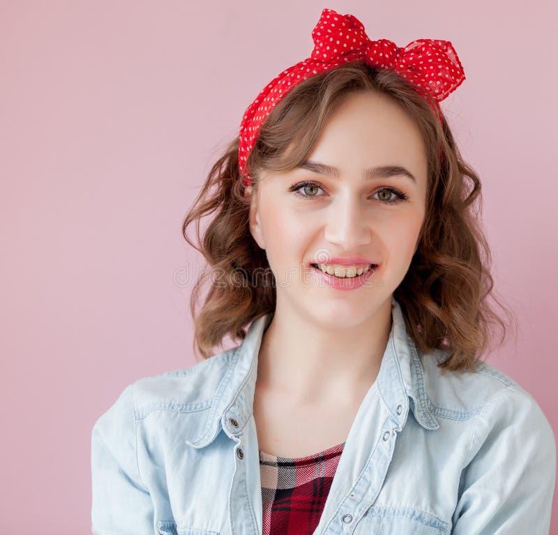 Belle jeune femme avec le maquillage et la coiffure de goupille- Studio tiré sur le fond rose photo libre de droits