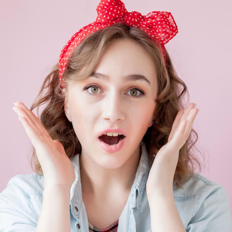 Belle jeune femme avec le maquillage et la coiffure de goupille- Studio tir? sur le fond rose images libres de droits