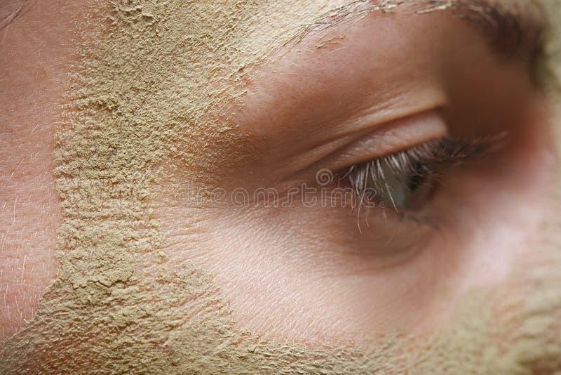 Belle jeune femme avec le masque de massage facial d'argile images stock