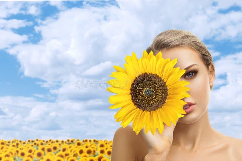 Belle jeune femme avec le tournesol dans des ses mains photos stock