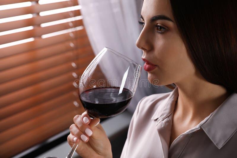 Belle jeune femme avec le verre de vin rouge de luxe à l'intérieur, vue de plan rapproché photos libres de droits