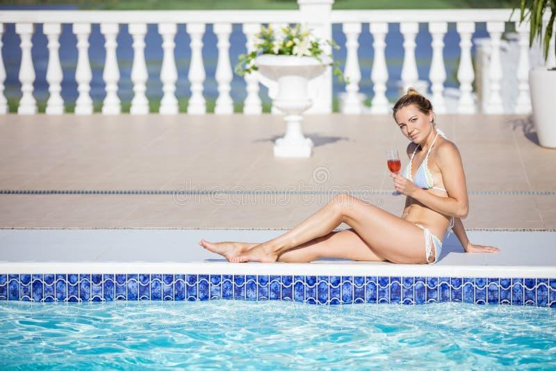Belle jeune femme avec le verre de vin se reposant par le poolside photographie stock