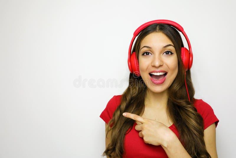 Belle jeune femme avec les écouteurs rouges écoutant la musique souriant et dirigeant l'espace de copie sur un fond blanc dans un image libre de droits