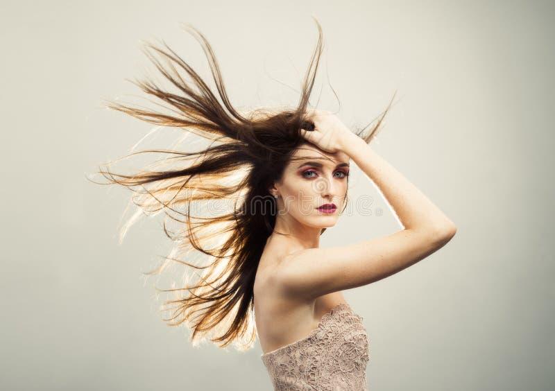 Belle jeune femme avec les cheveux balayés par le vent image stock
