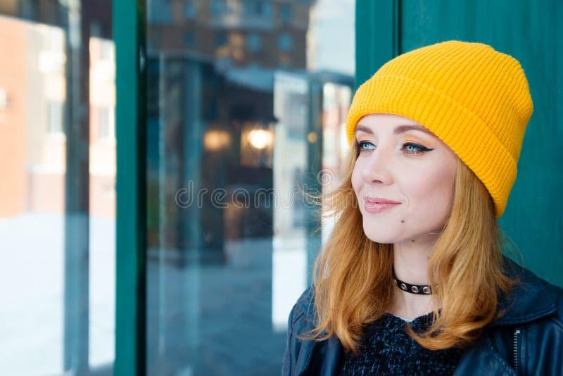 Belle jeune femme avec les cheveux blonds et les yeux bleus dans un chapeau de tricotage jaune sur un fond de mur vert photographie stock libre de droits