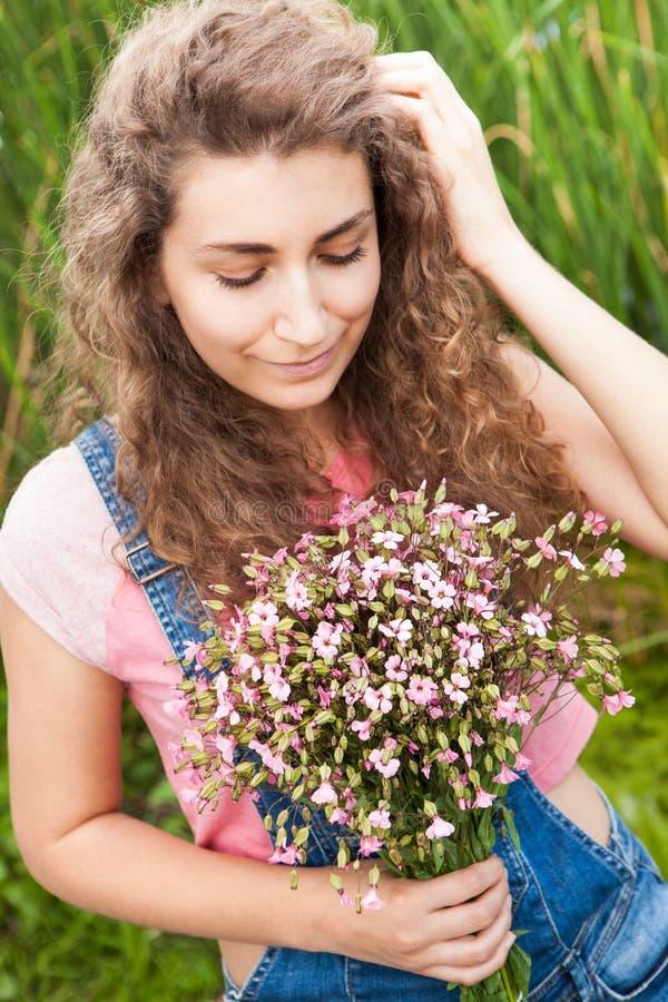 Belle jeune femme avec les cheveux bouclés avec le bouquet des fleurs roses regardant vers le bas photo stock
