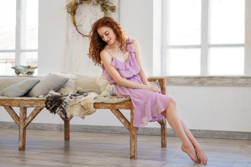 Belle jeune femme avec les cheveux rouges se reposant dans le studio photographie stock libre de droits