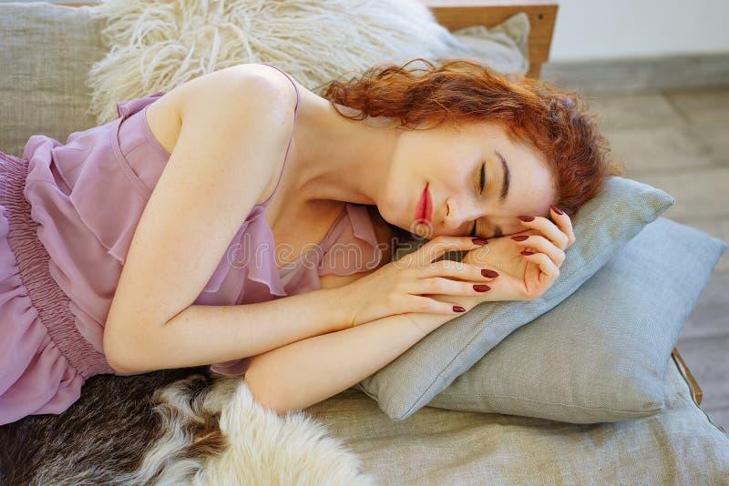 Belle jeune femme avec les cheveux rouges se trouvant sur le divan photo stock