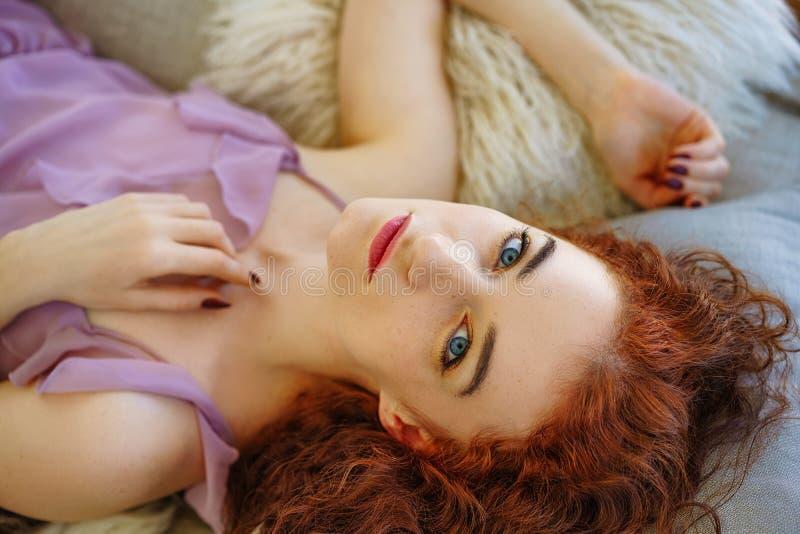 Belle jeune femme avec les cheveux rouges se trouvant sur le divan photographie stock