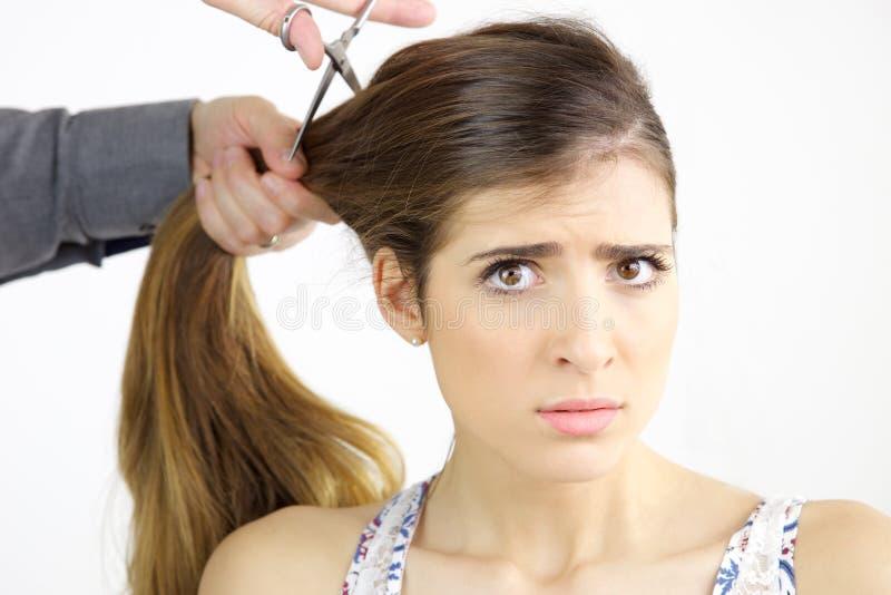 Belle jeune femme avec les cheveux très longs déçus tout en obtenant la coupe de cheveux photo stock
