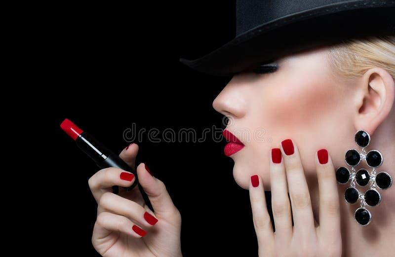 Belle jeune femme avec les lèvres et la manucure rouges image stock