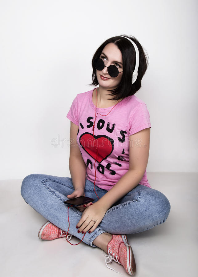 Belle jeune femme avec les lunettes de soleil et les écouteurs ronds bleus Glaces émouvantes photo libre de droits