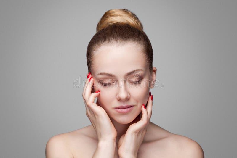 Belle jeune femme avec les yeux fermés de peau fraîche propre soin rouge de manucure et d'ongle soin femelle de visage de beauté  image stock
