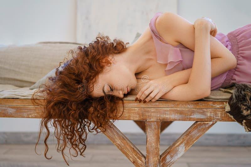 Belle jeune femme avec se reposer rouge de cheveux triste photographie stock libre de droits