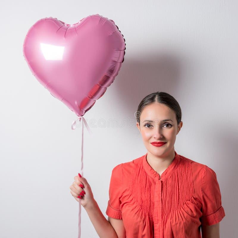 Belle jeune femme avec un ballon en forme de coeur sur un fond lumineux Concept de jour du ` s de Valentine photo stock