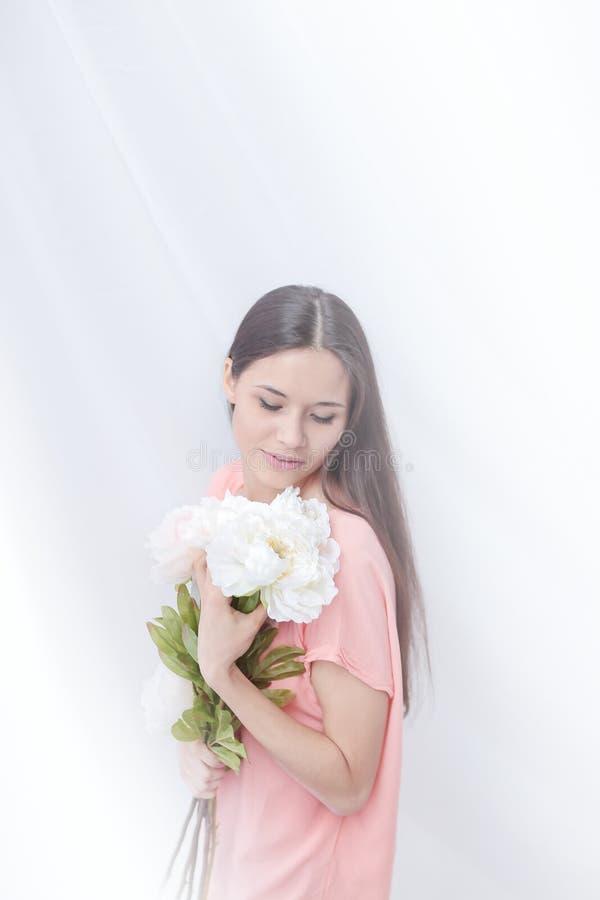 Belle jeune femme avec un bouquet des pivoines Photo avec l'espace de copie photographie stock