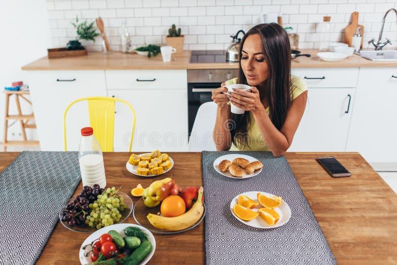 Belle jeune femme avec une tasse de café à la maison sur le fond de cuisine photo stock