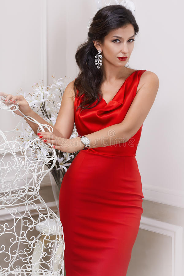 Belle jeune femme bien-toilettée luxueuse sexy dans des boucles d'oreille furtives rouges d'une robe avec les diamants et le long photos stock