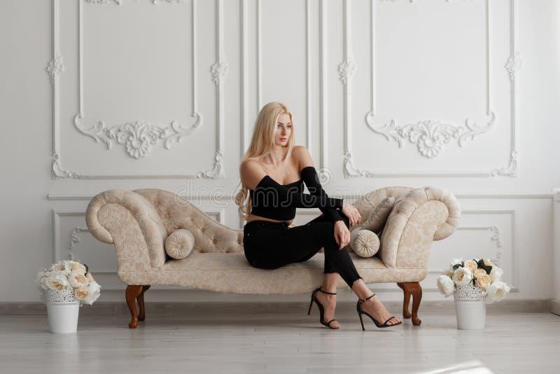 Belle jeune femme blonde élégante dans des vêtements noirs de mode images libres de droits