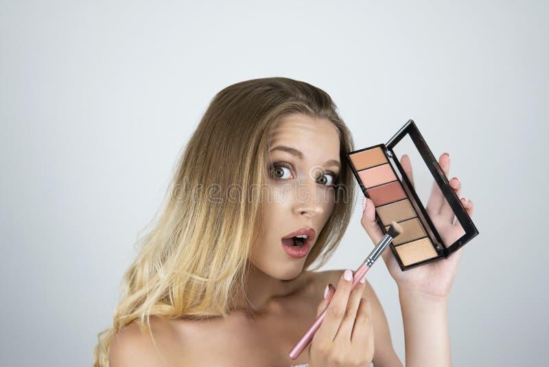Belle jeune femme blonde appliquant le fard à paupières sur le fond blanc d'isolement par brosse photographie stock
