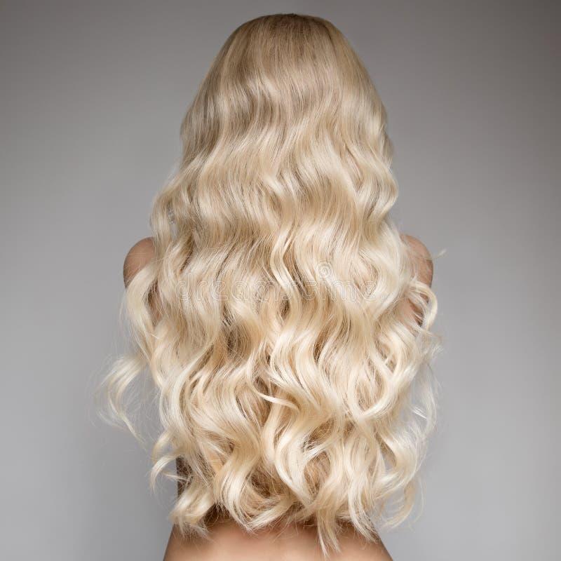 Belle jeune femme blonde avec de longs cheveux onduleux photographie stock