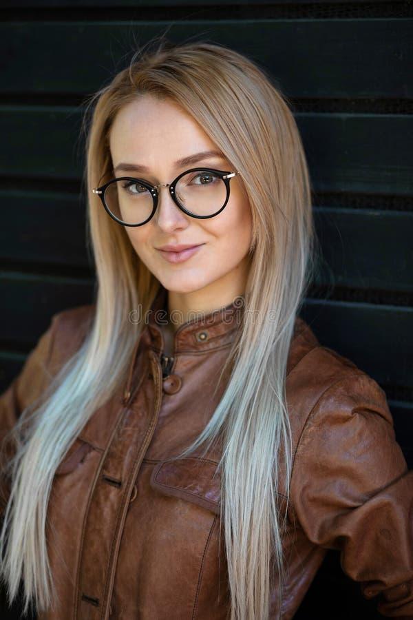 Belle jeune femme blonde avec les verres élégants extérieurs sur le fond foncé Concept des verres de port de jeune fille et photographie stock