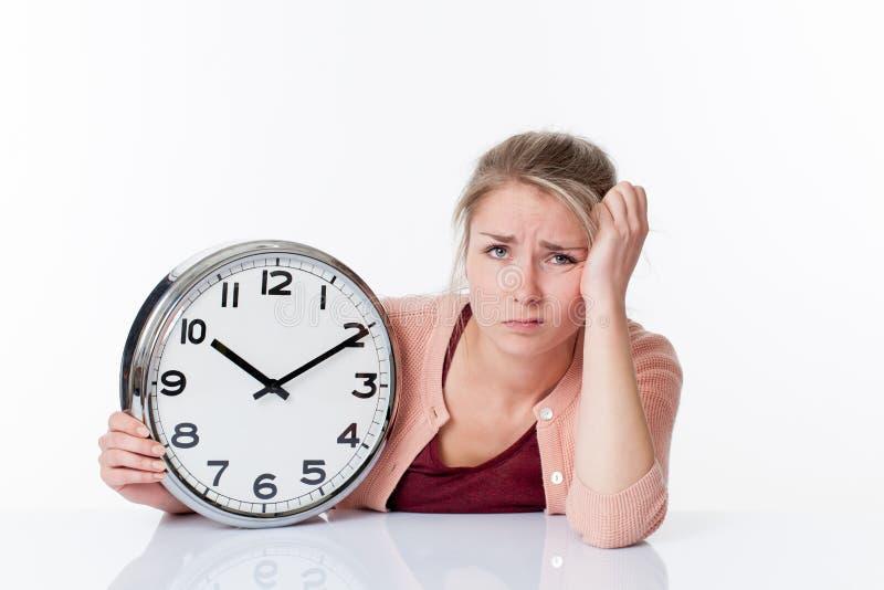 Belle jeune femme blonde désillusionnée tenant une horloge image stock